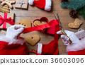 Santa Claus wrapping up Christmas gifts  36603096