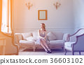 Young pregnant woman in white dress sitting 36603102