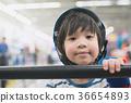 Boy in blue helmet standing with stadium  36654893