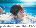 Boy swimming and playing in a pool 36654922