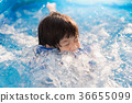 Boy swimming and playing in a pool 36655099