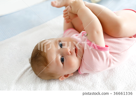 Cute baby taking feet in mouth. Adorable little 36661336