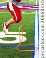 High school football player jumping hurdles 36668316