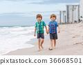Two little kids boys running on the beach of ocean 36668501