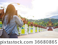 Female tourist taking picture of Buddhist temple  36680865