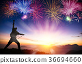 man on mountain and watching sunrise and fireworks 36694660