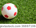 Toy red and white color football on green grass 36697106