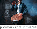 Male drummer playing on wooden drum 36698748
