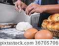 Close up of Man hands sprinkling flour over fresh dough with ing 36705706