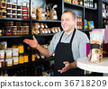 salesman working in delicatessen section of ordinary grocery 36718209