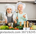 Two girls preparing vegetables and smiling indoors 36719245