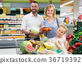 Parents with daughter choosing vegetables 36719392