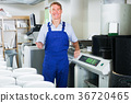 man seller standing with goods lift in housewares hypermarket 36720465