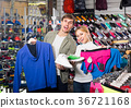 Couple trying items in the sport shop. 36721168