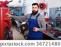 Positive male worker repairing motorbike 36721480