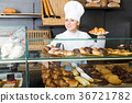 Girl offering desserts in the pastry shop . 36721782