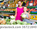 woman with girl buying cabbage 36721840
