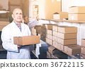 Portrait of different ages couple with carton boxes in warehouse 36722115