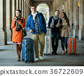 travelers with baggage sightseeing and smiling in autumn 36722609