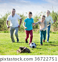 Mother and father with two kids running after ball 36722751