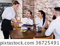 Charming young waiter receiving order from guests 36725491