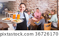 Cheerful waitress holding tray with dishes meeting visitors 36726170