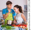 Couple at kitchen with vegetables at the table. 36726519