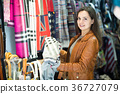 Woman choosing scarf in shop 36727079