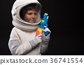 Pleasant kid cosmonaut is playing with toy gun 36741554