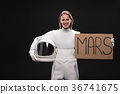Cheerful female cosmonaut is standing with 36741675