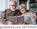 Charming senior couple relaxing on sofa with book 36742640