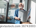 Pensive senior aged man sitting on windowsill 36743003