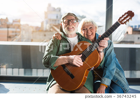 Full of life mature couple sitting at window with 36743245