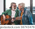 Playful aged couple relaxing at home with musical 36743476
