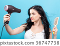 Beautiful woman holding a hairdryer  36747738