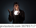 Young wizard with crystal ball in dark room 36765717
