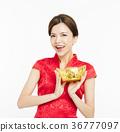 woman wear cheongsam and showing  gold ingot 36777097