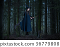 Witch flying on a broom in the forest 36779808