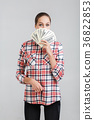 woman in a plaid shirt holding dollar bills 36822853