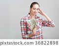 woman in a plaid shirt holding dollar bills 36822898