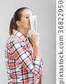 woman in a plaid shirt holding dollar bills. 36822950