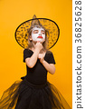 Small girl in Halloween witch costume, orange 36825628
