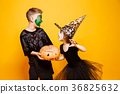 Kids in Halloween Costumes Playing with Pumpkin 36825632