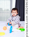 baby playing with toy on bed 36826963