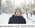 Beautiful young girl in a white winter forest 36829584