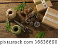 Overhead view of pine cones with gift boxes and thread spools 36836690