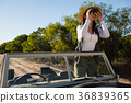 Young woman looking through binoculars standing in off road vehicle 36839365