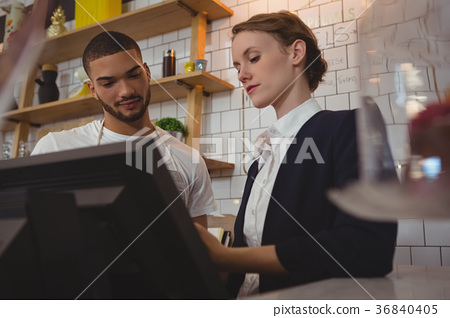 Female owner with waiter using cash register in cafe 36840405