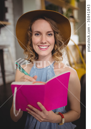 Portrait of smiling young woman holding pink dairy with pen 36841843