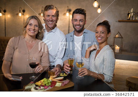 Portrait of happy friends having drinks and meal 36842571